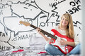 Full-length portrait of teenage girl playing guitar in bedroom Royalty Free Stock Photo