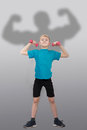 Funny slim boy with bodybuilder's silhouette behind him Royalty Free Stock Photo
