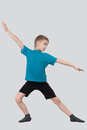 Full length portrait of ten year old boy warming up on grey background Royalty Free Stock Images