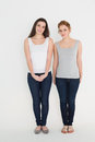 Full length portrait of two casual young female friends standing against white background Stock Photo