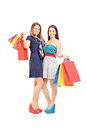 Full length portrait of two female friends holding shopping bags and posing isolated on white background Royalty Free Stock Photo