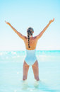 Full length portrait of woman standing in sea and rejoicing young rear view Royalty Free Stock Image