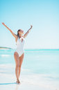 Full length portrait of woman walking rejoicing on sea shore young Stock Image