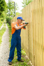 Full-length portrait of worker constructing wooden fence Royalty Free Stock Photo