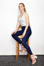 Full length portrait of young beautiful redhead beginner model woman in white t-shirt blue jeans practicing posing showing emotion Royalty Free Stock Photo