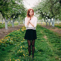 Full length portrait of young beautiful redhead woman in an apple garden blossoming Royalty Free Stock Photos