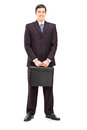 Full length portrait of a young businessman with a briefcase pos posing isolated on white background Stock Photography