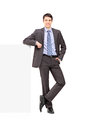 Full length portrait of a young businessman posing on a panel blank isolated white background Royalty Free Stock Image
