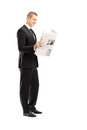 Full length portrait of a young businessman reading a newspaper isolated on white background Royalty Free Stock Image