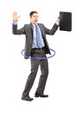 Full length portrait of a young businessman in suit holding a briefcase and dancing with a hula hoop isolated on white background Stock Photography
