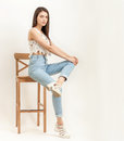 Full length portrait of young calm beautiful brunette woman posing for model tests against white background sitting on bar stool Royalty Free Stock Photo