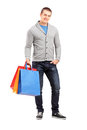 Full length portrait of a young casual man holding shopping bags Royalty Free Stock Photo