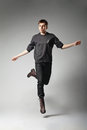 Full length portrait young fashion male jumping grey background Royalty Free Stock Images