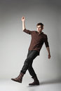 Full length portrait young fashion male jumping grey background Royalty Free Stock Photo