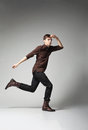Full length portrait young fashion male jumping grey background Stock Photos