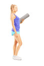 Full length portrait of a young female athlete holding an exerci exercising mat and posing isolated on white background Royalty Free Stock Images