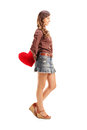 Full length portrait of a young female holding a red heart behin behind and looking isolated on white background Stock Image