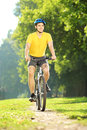 Full length portrait of a young man biking in a park yellow shirt Stock Photos
