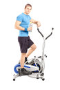 Full length portrait of a young man posing on a cross trainer fi fitness machine isolated white background Stock Photos