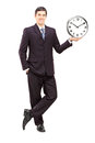 Full length portrait of a young man in suit holding a clock isolated on white background Stock Photo
