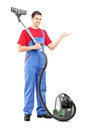 Full length portrait of a young man with a vacuum cleaner gesturing with his hand isolated on white background Royalty Free Stock Image