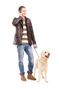 Full length portrait of a young man walking a dog and talking on mobile phone isolated white background Royalty Free Stock Photos