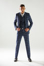 Full length portrait of young man wearing checked suit Royalty Free Stock Photo