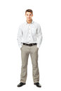 Full length portrait of young man wearing white shirt and light trousers with hands in pockets isolated on white background Stock Photos
