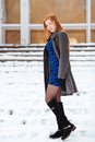 Full length portrait of young pretty redhead woman in blue dress and grey coat at winter outdoors Royalty Free Stock Photo