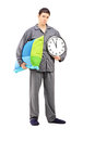 Full length portrait of young sleepy guy holding a wall clock an and pillow isolated on white background Stock Photography