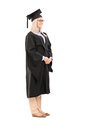 Full length portrait of young woman in graduation gown Stock Images