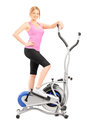 Full length portrait of a young woman posing on a cross trainer fitness machine isolated white background Royalty Free Stock Photos