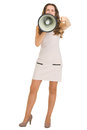 Full length portrait of young woman shouting through megaphone and pointing in camera Royalty Free Stock Images