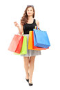 Full length portrait of a young woman walking with shopping bags isolated on white background Stock Image