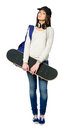 Full length portrait of youngster with skateboard teenager wearing peaked cap headphones and rucksack isolated on white concept Royalty Free Stock Photography