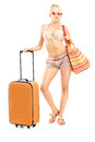 Full length portriat of a female tourist in bikini with a suitca suitcase isolated on white background Royalty Free Stock Image