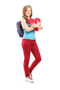 Full length potrait of a female student with backpack holding a red heart isolated on white background Royalty Free Stock Images