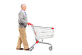Full length potrait of a gentleman walking and pushing an empty shopping cart isolated on white background Stock Images