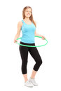 Full length potrait of a young female athlete exercising with a hula hoop isolated on white background Royalty Free Stock Photos