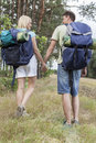 Full length rear view of young backpackers holding hands in countryside Stock Images