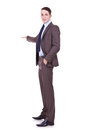 Full length of successful business man presenting Royalty Free Stock Photo