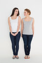 Full length of two casual young female friends standing against white background Stock Image