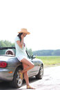 Full-length of woman using cell phone while leaning on convertible at countryside Royalty Free Stock Photo
