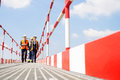 Full-length of workers walking on footbridge against sky Royalty Free Stock Photo