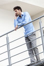 Full length of young businessman using cell phone at hotel balcony Royalty Free Stock Photo