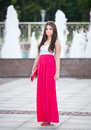 Full length of young caucasian female with long red skirt standing in front of a fountain outdoor romantic portrait the woman Stock Images