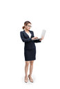 Full length of a young female businesswoman holding laptop over grey background. Royalty Free Stock Photo