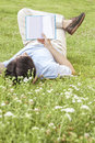 Full length of young man holding book while lying on grass in park Royalty Free Stock Photo