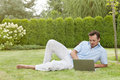 Full length of young man using laptop while reclining in park Royalty Free Stock Photo