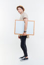 Full length of young man walking and holding blank whiteboard Royalty Free Stock Photo